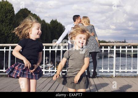 Mädchen im Freien spielen, während ihre Eltern im Hintergrund küssen - Stockfoto