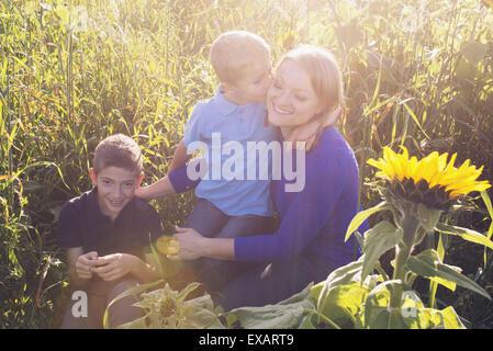 Mutter und jungen Söhne, Zeit miteinander zu verbringen, im Feld von Sonnenblumen - Stockfoto