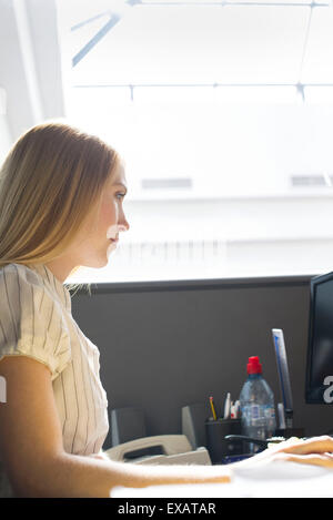 Junge Frau aufmerksam im Großraumbüro arbeiten - Stockfoto