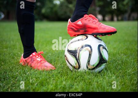 Nahaufnahme eines kleinen Jungen mit seinem Fuß auf einem Fußball - Stockfoto
