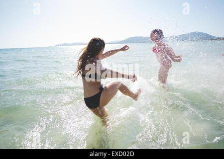 Gruppe von multiethnischen Jugendliche Frauen und Männer am Strand im Sommer Spaß im Wasser plantschen - Stockfoto