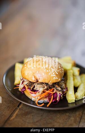 Wir fuhren Schweinefleisch und Krautsalat Burger mit dicken Pommes frites - Stockfoto