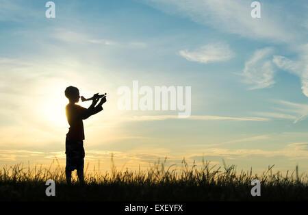Junge werfen ein Modellflugzeug bei Sonnenuntergang. Silhouette - Stockfoto