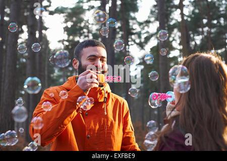 Junges Paar blowing Bubbles zusammen im Wald - Stockfoto