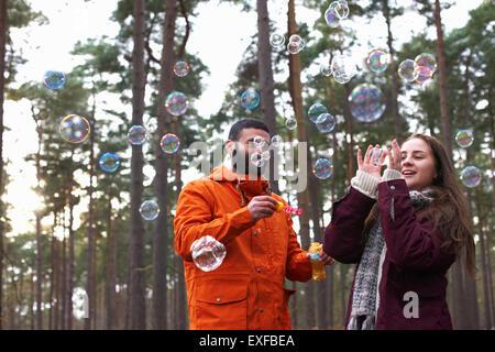Junges Paar Seifenblasen im Wald - Stockfoto