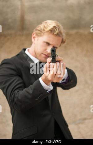 Mann mit dem Ziel, einer Pistole, bereit zu schießen, trägt einen schwarzen Anzug. - Stockfoto