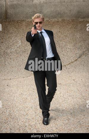 Mann zu Fuß in Richtung jemand eine Waffe, bereit zu schießen, trägt einen schwarzen Anzug. - Stockfoto