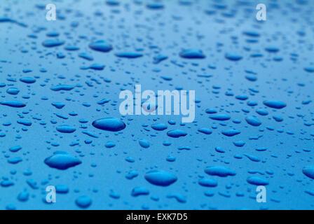 Wassertropfen auf blauem Untergrund - Stockfoto