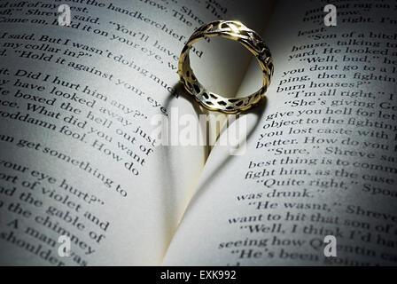 Ring mit herzförmigen Schatten auf ein offenes Buch liegend - Stockfoto
