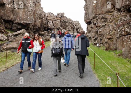 Touristen gehen durch die Almannagja Bruchlinie in der mid-Atlantic Ridge nordamerikanische Platte Thingvellir National - Stockfoto