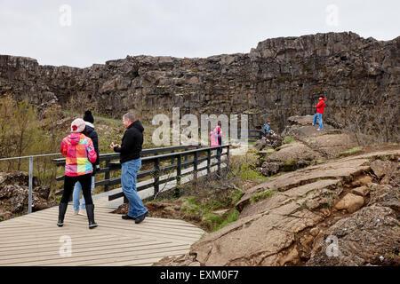 Touristen gehen durch die Almannagja Bruchlinie in der mid-Atlantic Ridge nordamerikanische Platte Thingvellir National - Stockfoto