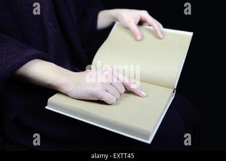 weibliche Hände halten ein offenes Buch - Stockfoto
