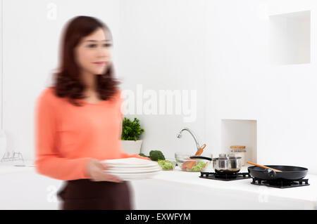 Junge Frau mit Platten in der Küche, - Stockfoto
