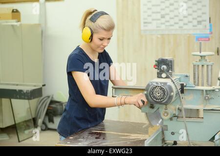 Junge Frau arbeitete in einer Tischlerei auf einer buzzsaw - Stockfoto