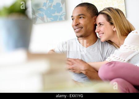 Mitte erwachsenes paar umarmt im Wohnzimmer - Stockfoto