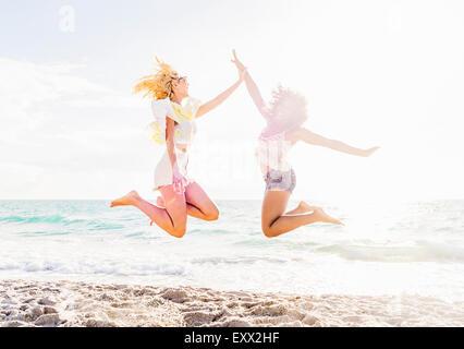 Freundinnen am Strand springen - Stockfoto