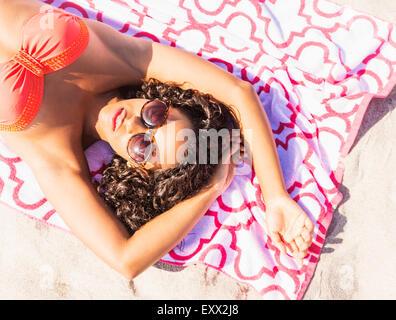 Junge Frau, Sonnenbaden am Strand - Stockfoto