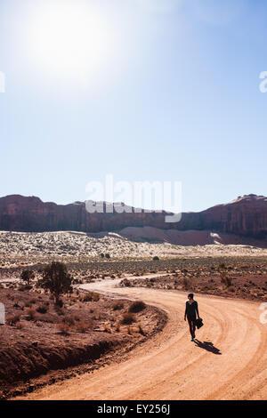 Mitte Erwachsene Frau zu Fuß entlang des ländlichen Raums Feldweg, Monument Valley, Utah, USA - Stockfoto
