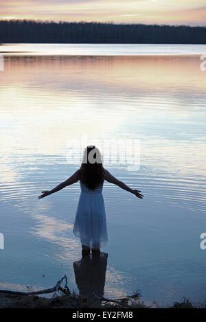 Eine Frau in einem weißen Kleid im seichten Wasser in der Abenddämmerung