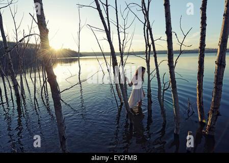 Eine Frau in einem weißen Kleid im seichten Wasser in der Abenddämmerung - Stockfoto