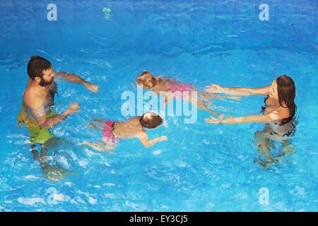 Glückliche Familie - Vater und Mutter im blauen Pool mit Babys unter Wasser schwimmen mit Spaß. Gesunder Lebensstil, - Stockfoto