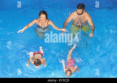 Glückliche Familie - Vater und Mutter im blauen Pool mit Babys Mädchen und jungen unter Wasser schwimmen mit Spaß. - Stockfoto