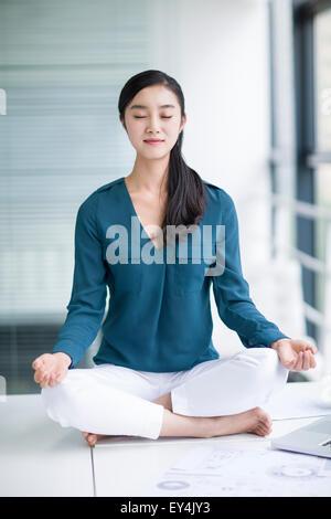 Junge Geschäftsfrau tun Yoga am Schreibtisch - Stockfoto