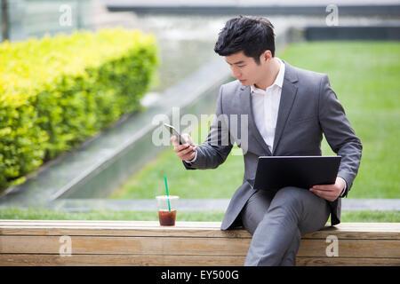 Junger Geschäftsmann mit Laptop im Freien arbeiten - Stockfoto