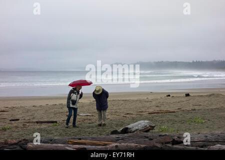 Älteres Paar zu Fuß am Strand von Wickanninish an einem regnerischen Sommertag.  Surfer in den Wellen des Ozeans - Stockfoto