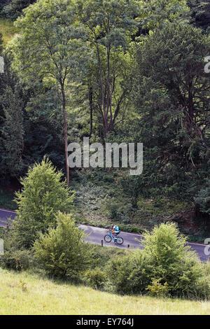 Radfahrer fährt entlang einer Landstraße, die von oben geschossen - Stockfoto
