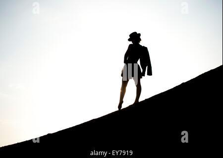 Eine junge Frau allein stehend in der Silhouette, einen Hut, mit ihrer Jacke über den Schultern - Stockfoto