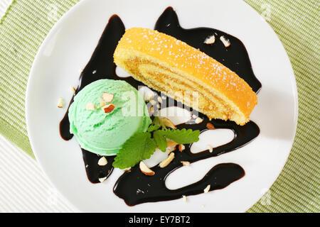 Biskuitrolle Kuchen mit grünen Sorbet und Schokoladensauce - Stockfoto