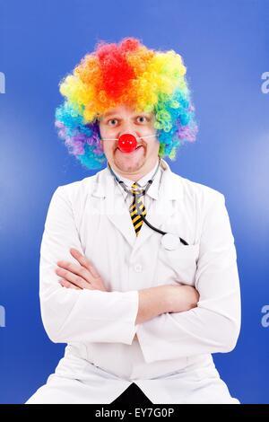 Lustiger Clown Doktor auf blau, tragen bunte Perücke und roter Ball Nase - Stockfoto