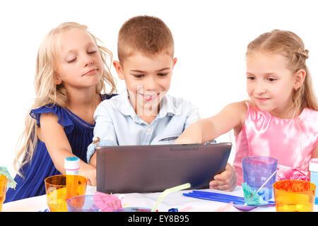 Verspielte Kinder sitzen mit laptop - Stockfoto