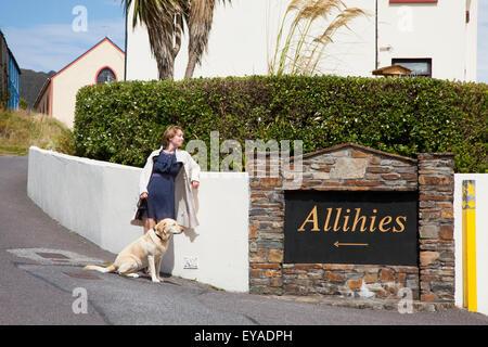 Eine Frau, die durch ein Schild für ihr Dorf mit ihrem Golden Retriever; Allihies, County Cork, Irland - Stockfoto
