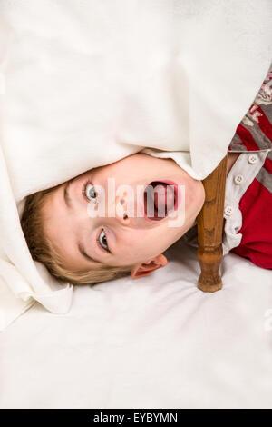 Sechs Jahre alten Jungen Spaß machen Gesichter unter einem überdachten Tisch - Stockfoto