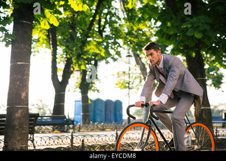 Geschäftsmann Reiten Fahrrad im Park morgen arbeiten - Stockfoto