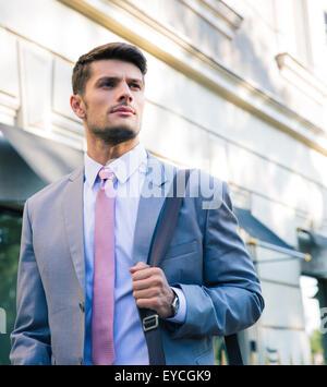 Porträt eines zuversichtlich jungen Geschäftsmann walking im Freien in der Stadt - Stockfoto