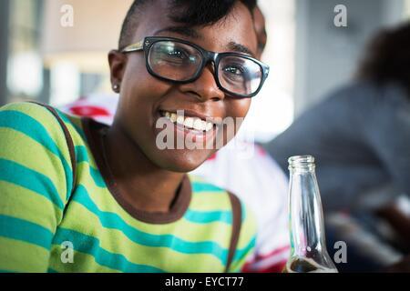 Junge Frau trinkt Bier in Flaschen auf Sofa im Wohnzimmer - Stockfoto