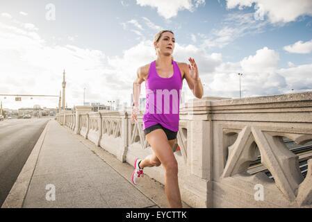 Junge weibliche Läufer laufen über Brücke, Los Angeles, Kalifornien, USA - Stockfoto
