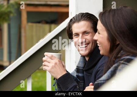 Junges Paar auf Veranda Schritt Kaffeetrinken - Stockfoto