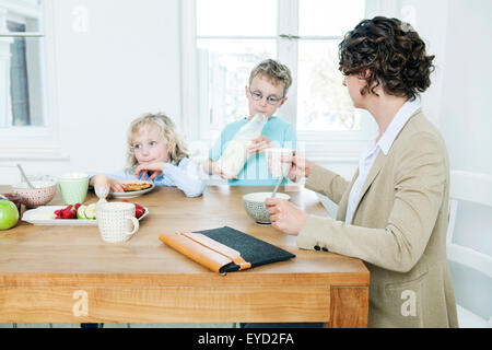 Mutter und zwei Kinder frühstücken - Stockfoto