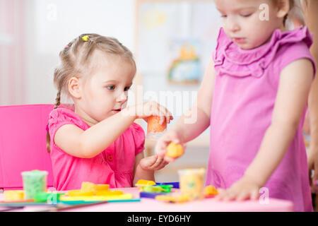 Mädchen spielen mit Plastilin in der Schule - Stockfoto