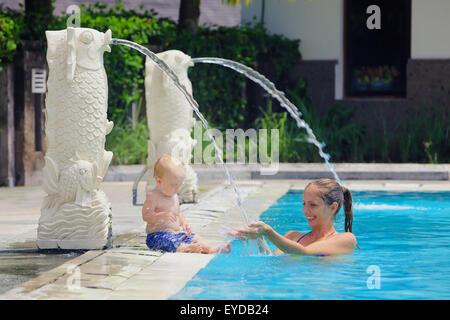 Kleinen Jungen ein Spaß und Lachen mit Mutter spielen mit Lächeln Spritzer im blauen Pool. - Stockfoto