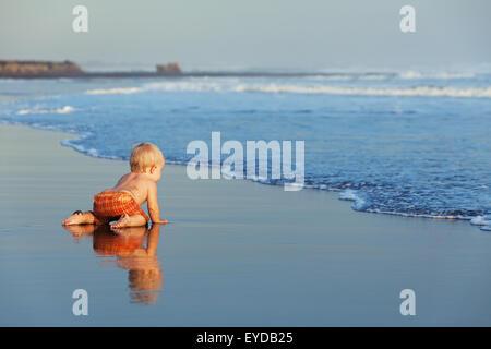 Der Sonnenuntergang Strand lustige Baby krabbeln auf schwarzen nassen Sand ins Meer zum Schwimmen in Wellen surfen. - Stockfoto