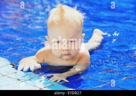 Gesicht-Porträt des kleinen Jungen spielen und Spaß im blauen Pool. Lehre unter Wasser schwimmen von Eltern. - Stockfoto