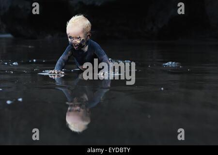 Im flachen Meer Strand schmutzig Baby krabbeln mit Spaß auf nassen schwarzen Sand ins Meer zum Schwimmen in Wellen - Stockfoto