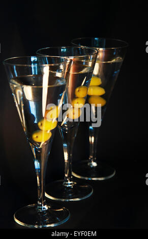 Drei Martini-Cocktails mit Oliven vor dem dunklen Hintergrund - Stockfoto