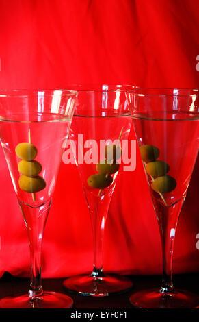 Drei Martini-Cocktails mit Oliven vor dem leuchtend roten Hintergrund - Stockfoto