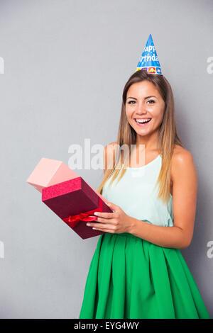 Lachende Mädchen Geschenkbox über grauen Hintergrund zu öffnen. Blick in die Kamera - Stockfoto